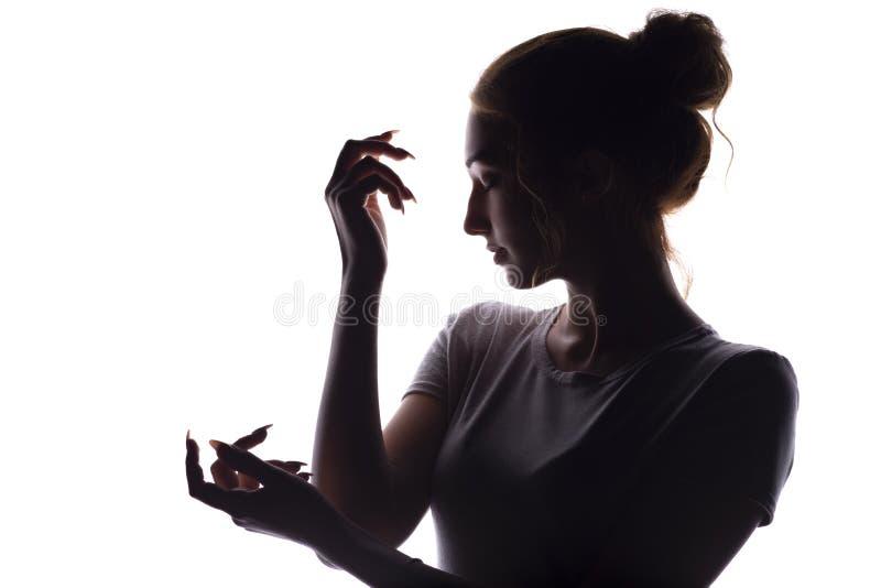 Silhouet van een jonge vrouw met elegant het gevouwen hand stellen voor kunst op wit geïsoleerde achtergrond, conceptenschoonheid royalty-vrije stock afbeeldingen