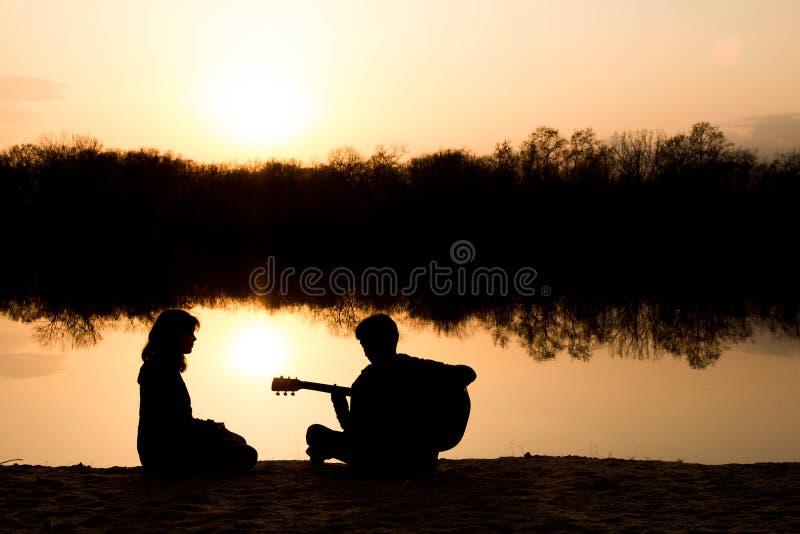 Silhouet van een jongen en een meisje op het strand met een gitaar stock afbeelding