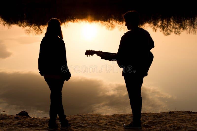 Silhouet van een jongen en een meisje op het strand met een gitaar royalty-vrije stock afbeelding