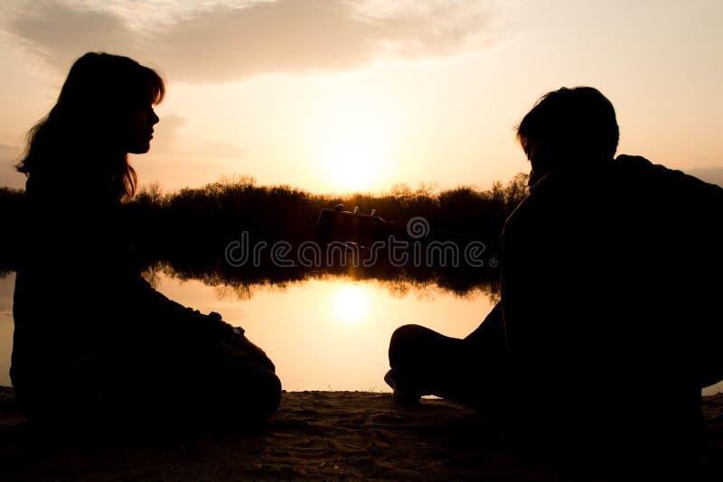 Silhouet van een jongen en een meisje op het strand met een gitaar royalty-vrije stock foto's