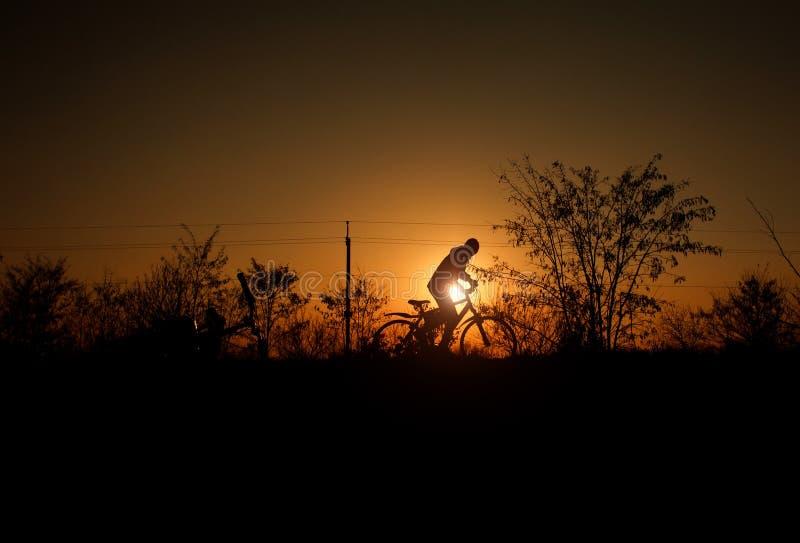 Silhouet van een jongen met fiets op achtergrond van heldere zonsondergangzon in uitstekende oude stijl royalty-vrije stock fotografie
