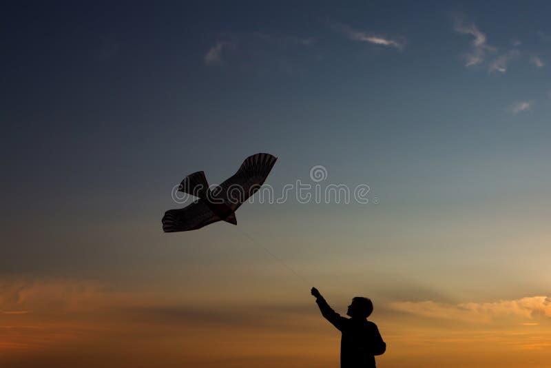 Silhouet van een jongen met een vlieger tegen de hemel Mooie zonsondergang, wolken De avond van de zomer royalty-vrije stock afbeeldingen