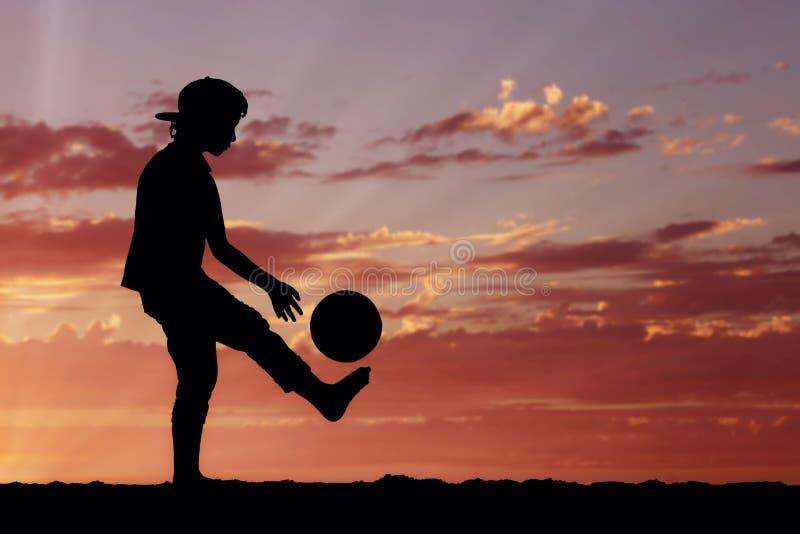 Silhouet van een jongens speelvoetbal of een voetbal bij royalty-vrije stock afbeeldingen