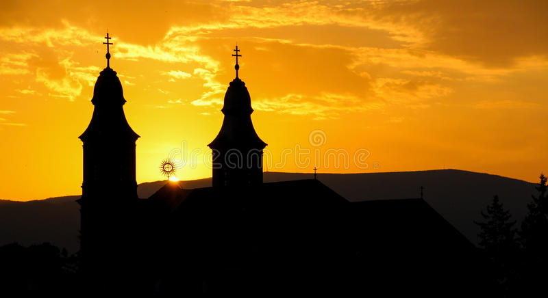 Silhouet van een katholieke kerk in zonsondergang stock foto's