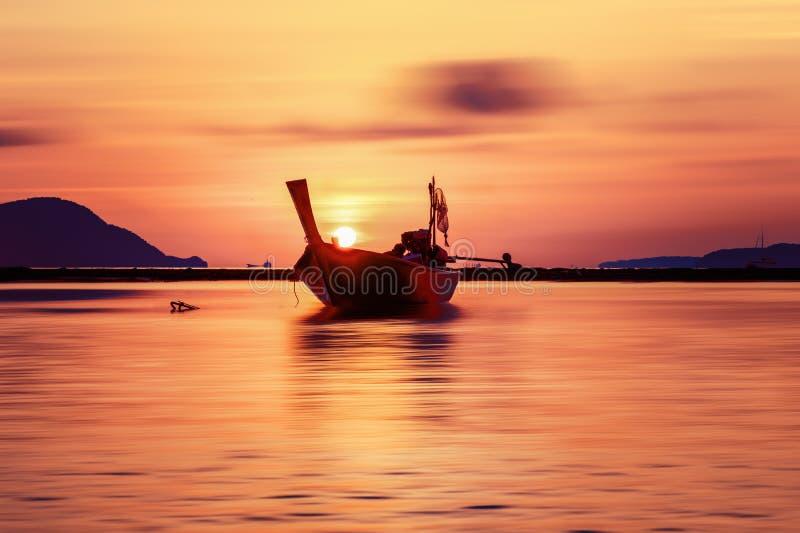 Silhouet van een kleine houten vissersboot in overzees met ochtend gouden hemel van zonsopgang royalty-vrije stock afbeelding