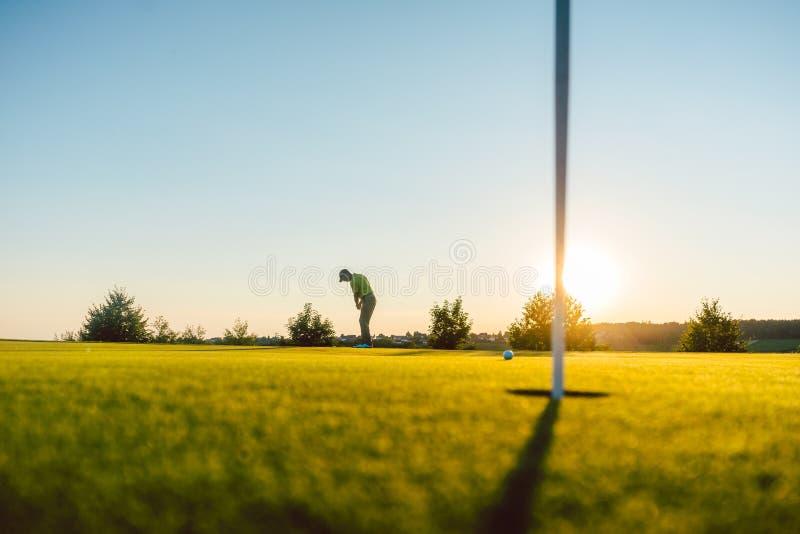 Silhouet van een mannelijke speler die een lang schot op de golfcursus raken stock foto's