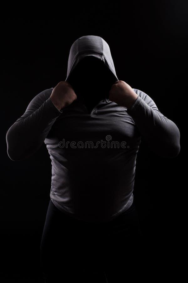 Silhouet van een mannelijke strijdclub in een kap zonder een gezicht Stalke royalty-vrije stock foto