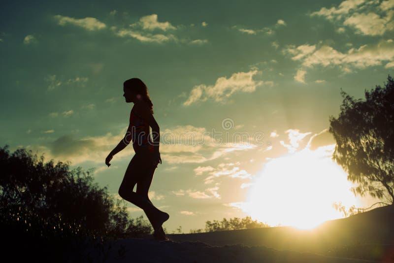 Silhouet van een meisje bij zonsondergang stock afbeelding