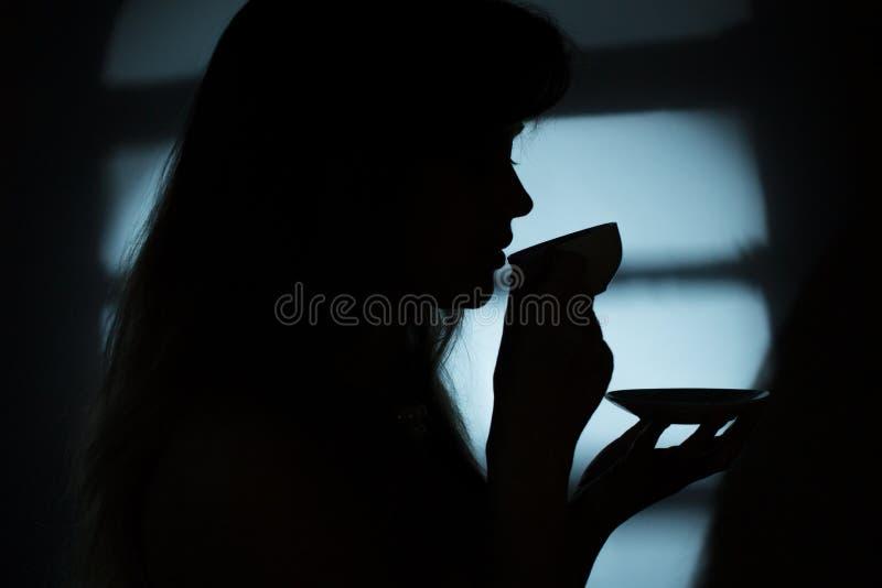 Silhouet van een meisje dichtbij een venster met een kop van hete drank royalty-vrije stock fotografie