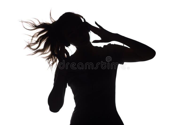 Silhouet van een meisje die aan muziek in hoofdtelefoons luisteren royalty-vrije stock foto