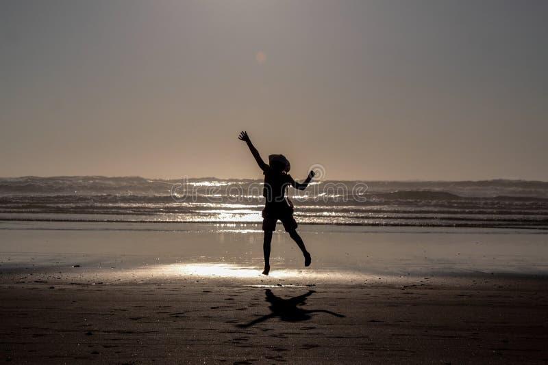 Silhouet van een meisje die hoog op een strand springen royalty-vrije stock afbeeldingen