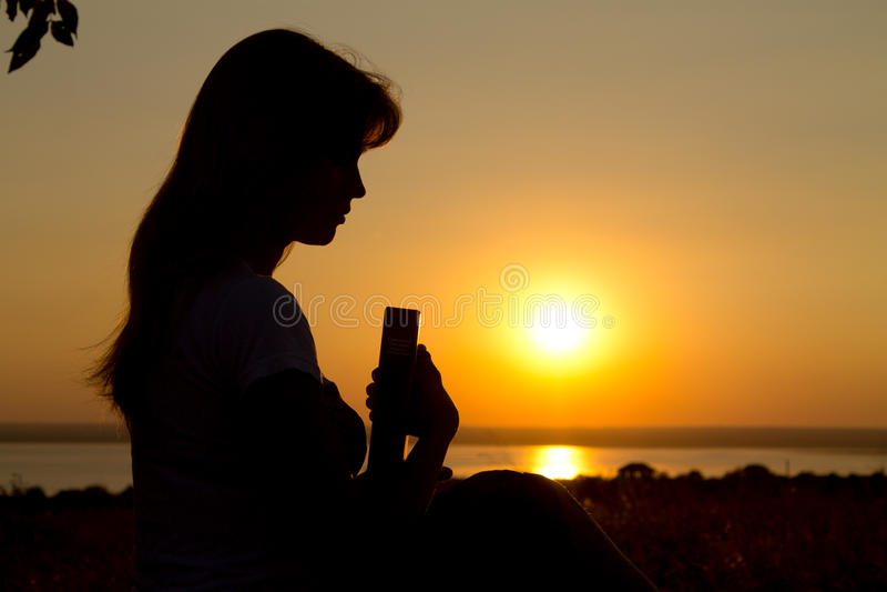 Silhouet van een meisje die met de Bijbel bidden royalty-vrije stock afbeeldingen