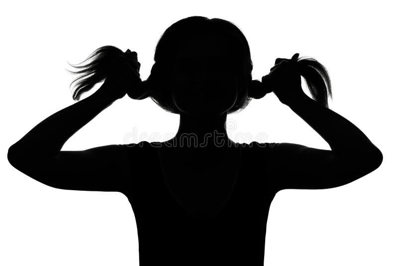 Silhouet van een meisje die met vlechten spelen stock foto