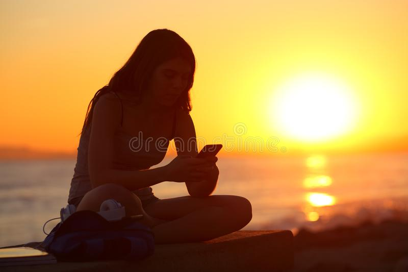 Silhouet van een meisje die een smartphone met behulp van bij zonsondergang royalty-vrije stock afbeelding