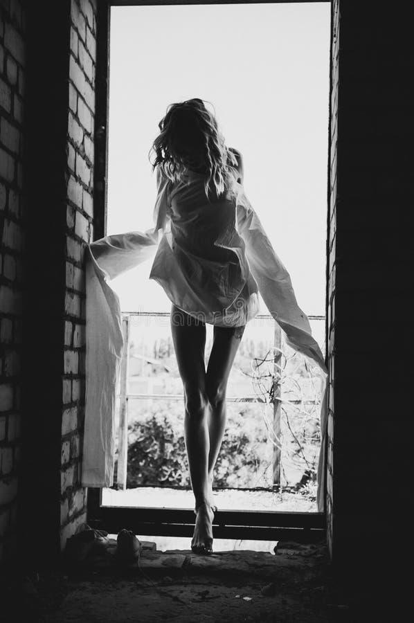 Silhouet van een meisje in een dwangbuis, mening van een deuropening royalty-vrije stock fotografie
