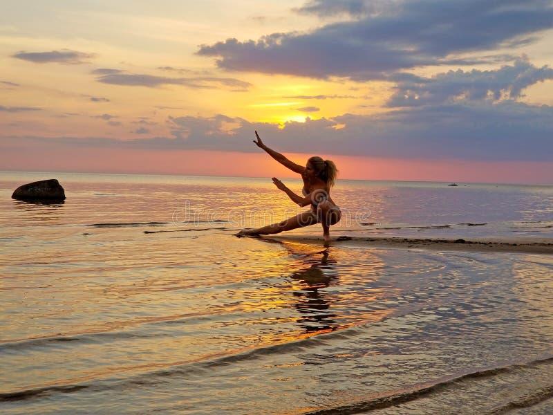 Silhouet van een meisje het praktizeren yoga op het strand Het schieten tegen de zon Zonsondergang over het overzees stock afbeelding