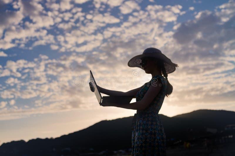 Silhouet van een meisje in een hoed en een kleding met laptop in haar handen, tegen de zonsondergang, de hemel en de bergen royalty-vrije stock afbeeldingen