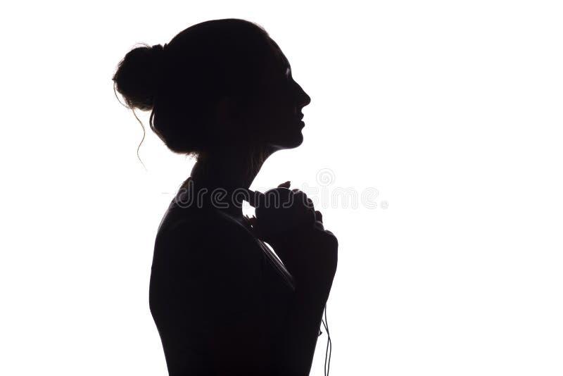 Silhouet van een meisje met met hoofdtelefoons rond hals, een jonge vrouw die aan muziek op een wit geïsoleerde achtergrond luist stock afbeelding