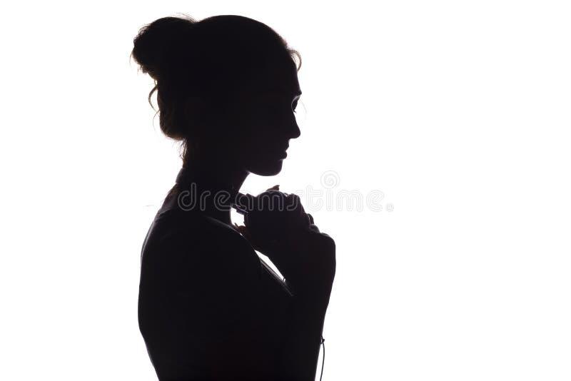 Silhouet van een meisje met met hoofdtelefoons rond hals, een jonge vrouw die aan muziek op een wit geïsoleerde achtergrond luist royalty-vrije stock foto's
