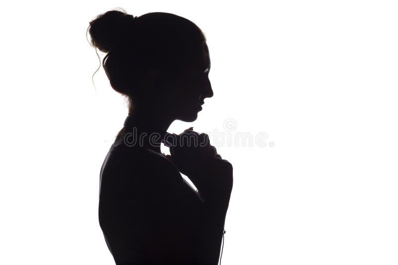 Silhouet van een meisje met met hoofdtelefoons rond hals, een jonge vrouw die aan muziek op een wit geïsoleerde achtergrond luist stock fotografie