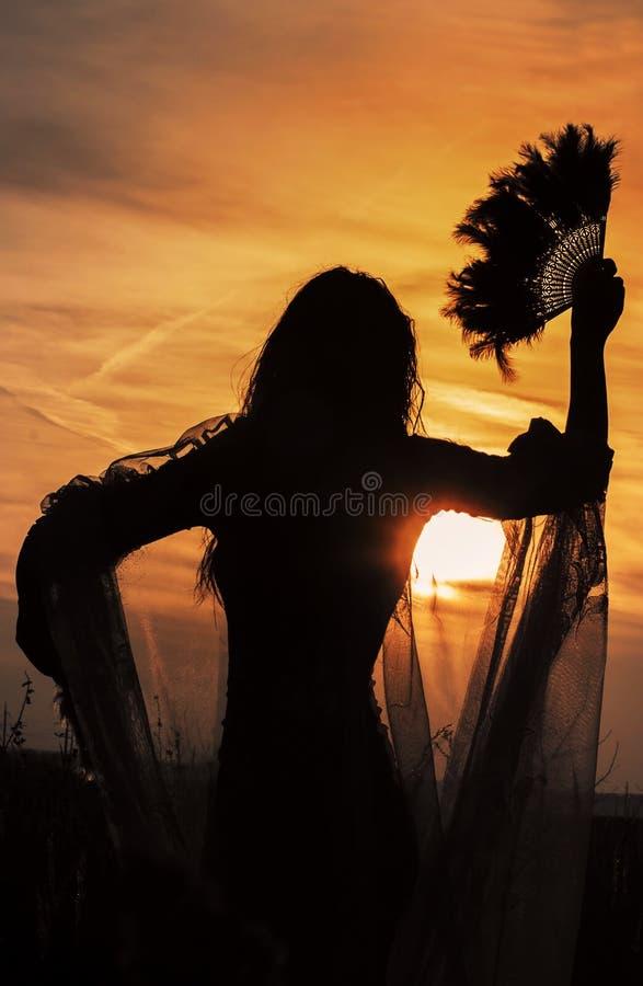 Silhouet van een meisje met een ventilator op een zonsondergangachtergrond royalty-vrije stock fotografie