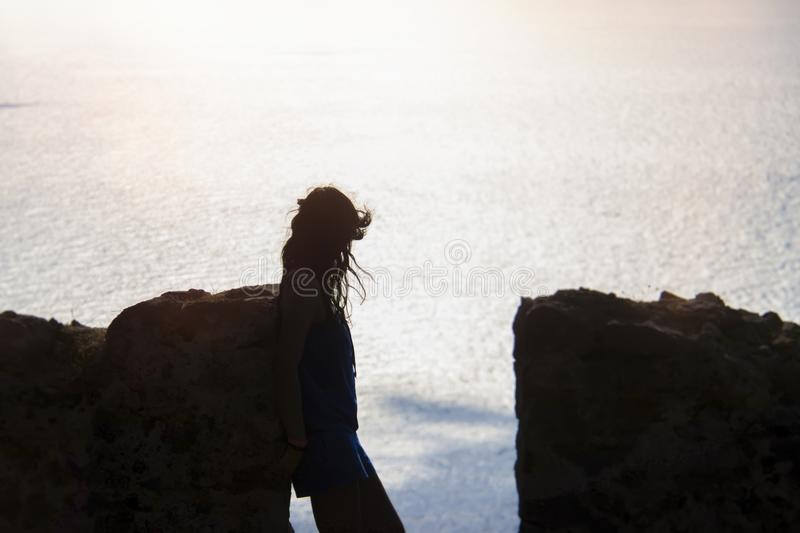 Silhouet van een meisje op de achtergrond van de overzeese achtergrond en steenmuur stock foto's