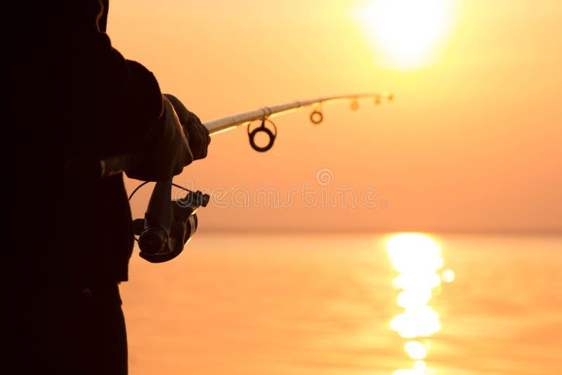 Silhouet van een meisje op de bank van de rivier met een hengel stock foto