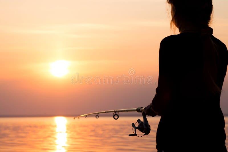 Silhouet van een meisje op de bank van de rivier met een hengel royalty-vrije stock foto's