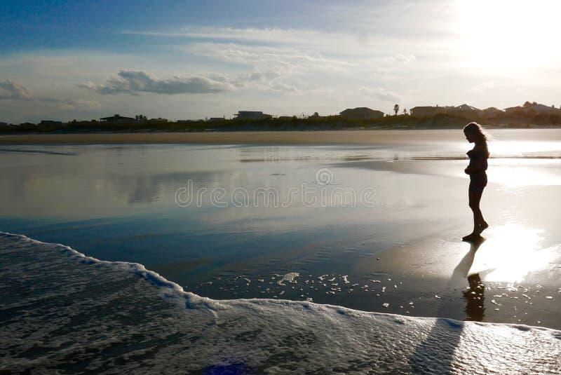 Silhouet van een meisje op het strand bij zonsondergang stock foto