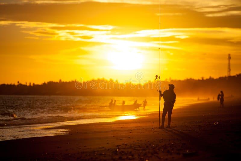 Silhouet van een meisje op het strand met een hengel in de zomer stock afbeelding