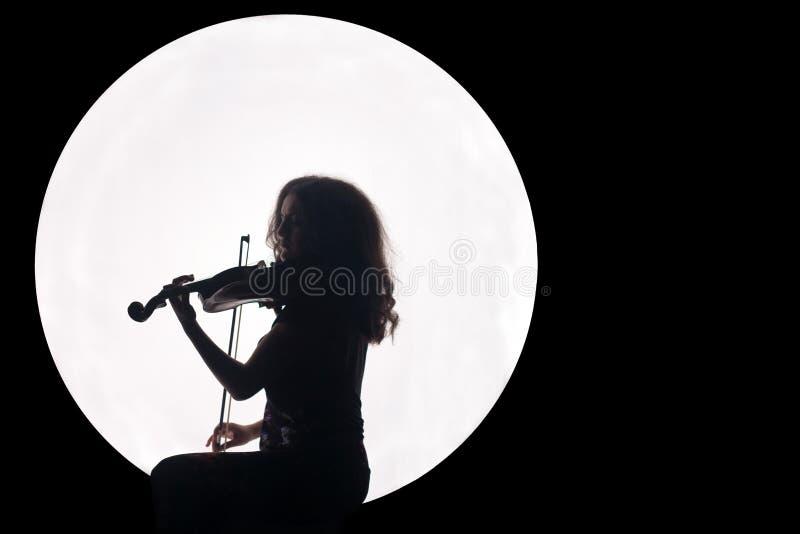 Silhouet van een meisje in een witte cirkel met een viool in haar handen Concept Muziek voor de volle maan Nachtachtergrond royalty-vrije stock afbeelding