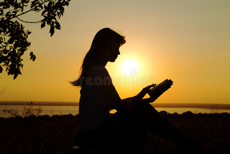 Silhouet van een meisjeslezing bij zonsondergang stock foto