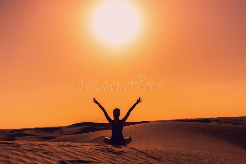 Silhouet van een meisjeszitting die op zand haar wapens opheffen omhoog tijdens de zonsondergang royalty-vrije stock foto
