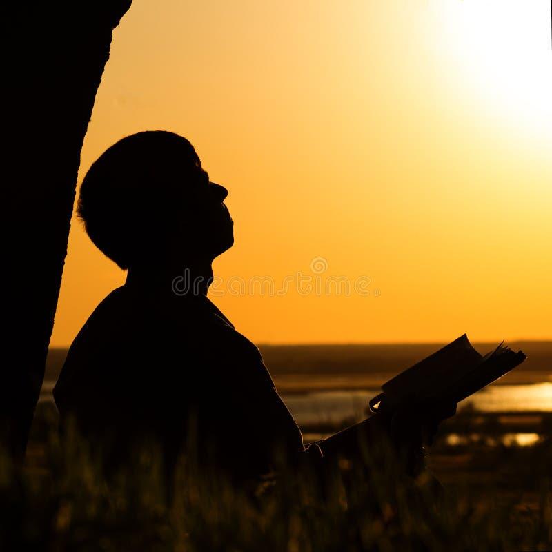 Silhouet van een mens die de Bijbel in het gebied, mannetje aan God in aard bidden, het concept godsdienst en spiritualiteit leze stock foto's