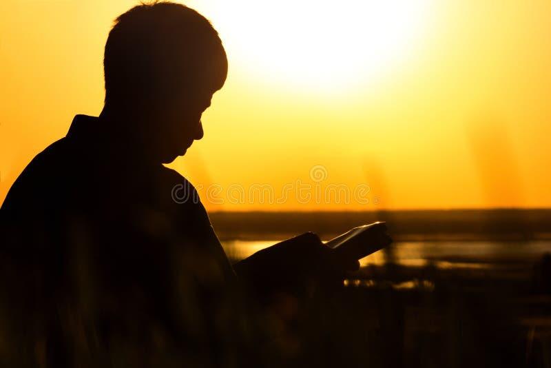 Silhouet van een mens die de Bijbel in het gebied, mannetje aan God in aard bidden, het concept godsdienst en spiritualiteit leze stock fotografie