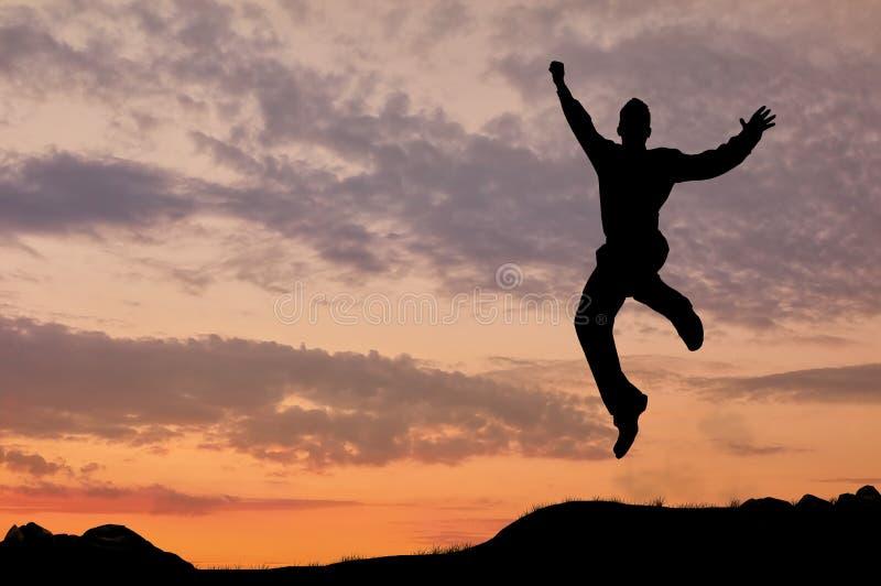 Silhouet van een mens die in de zonsondergang springen royalty-vrije stock foto