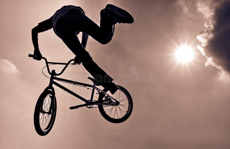 Silhouet van een mens die een extreme sprong van BMX doen stock afbeelding