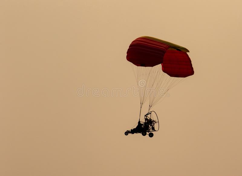 Silhouet van een mens die in een gemotoriseerd glijscherm vliegen royalty-vrije stock foto