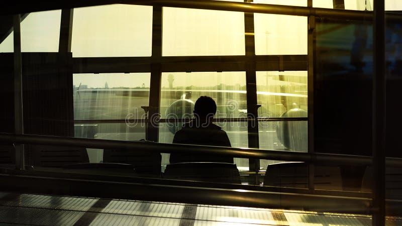Silhouet van een mens die op een vliegtuig aan vertrek met middagzonlicht wachten stock afbeelding