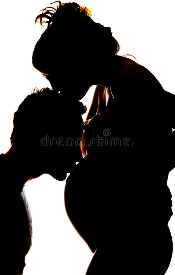 Silhouet van een mens die van Yong de buik van zijn zwangere vrouw kussen stock fotografie