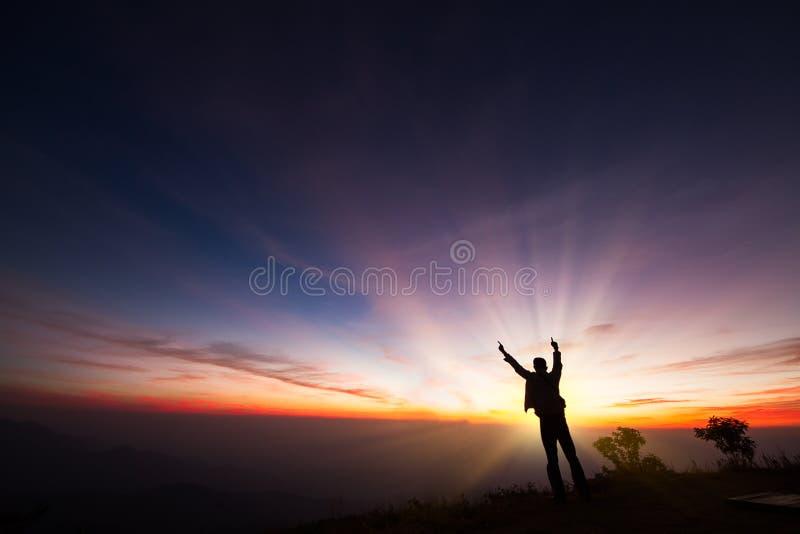 Silhouet van een mens die zich op de klip bevinden die zonsopgangbac bekijken royalty-vrije stock afbeelding