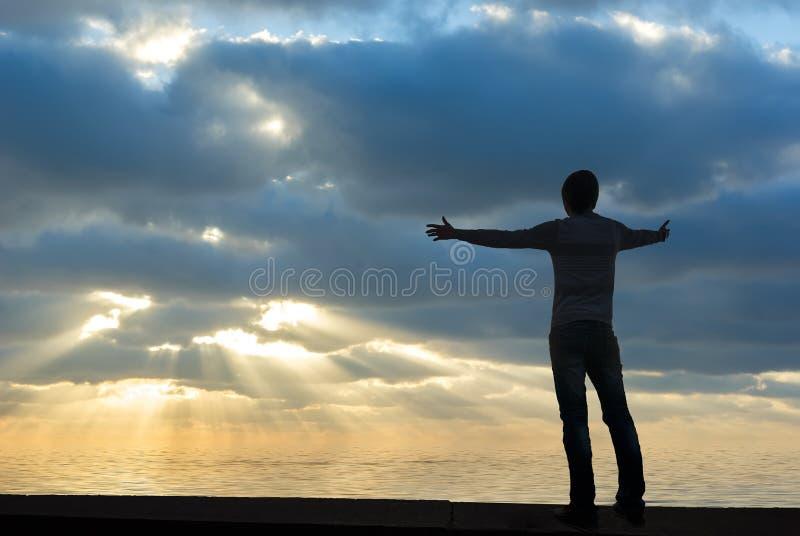 Silhouet van een mens die zijn handen opheft royalty-vrije stock afbeeldingen