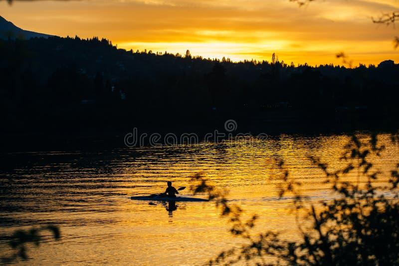 Silhouet van een mens in een kano bij zonsondergang royalty-vrije stock afbeeldingen