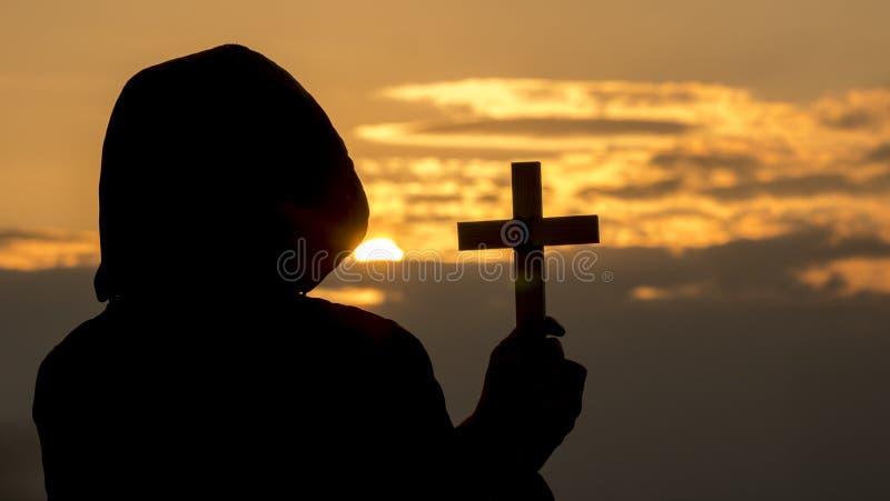 Silhouet van een mens in een kap met een kruisbeeld in zijn hand stock fotografie