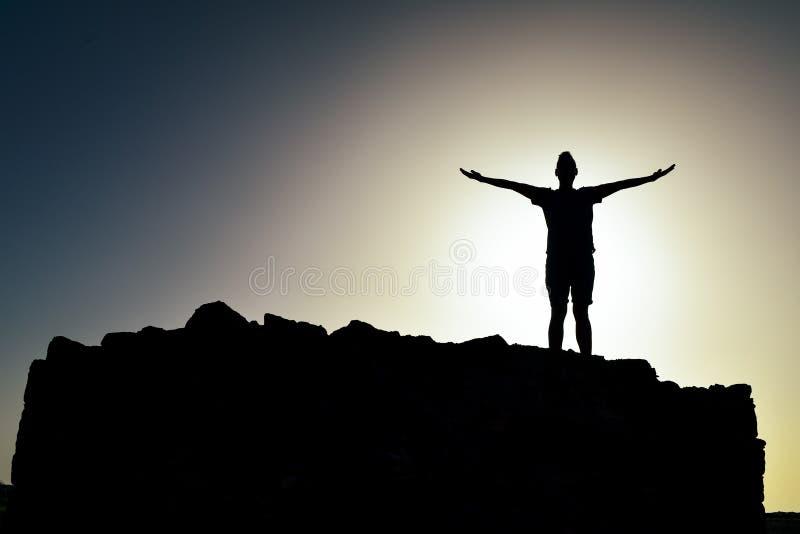 Silhouet van een mens met open wapens stock foto