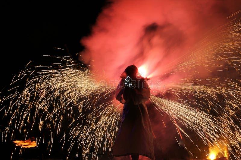 Silhouet van een mens op een achtergrond van het branden pyrotechniek stock afbeeldingen