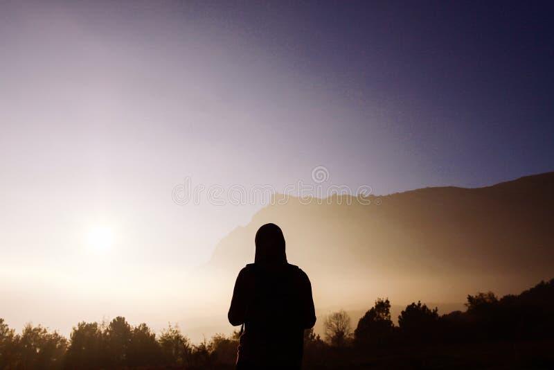Silhouet van een mens tegen de achtergrond van nevelige bergen Vrouwelijk silhouet op de achtergrond van nevelige bergen stock fotografie