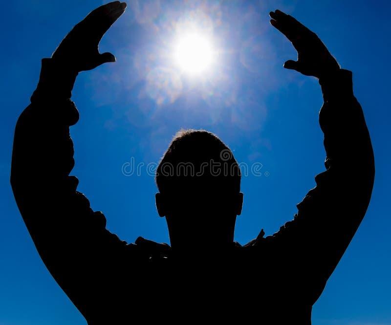 Silhouet van een mens tegen de achtergrond van de zon en de blauwe hemel De handen worden opgeheven tot de zon royalty-vrije stock afbeeldingen