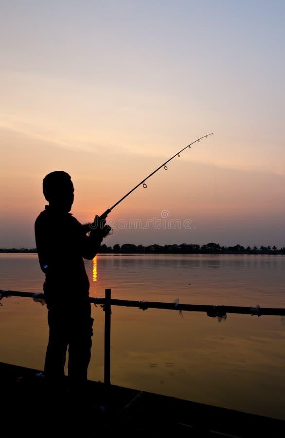 Silhouet van een mens visserij royalty-vrije stock afbeeldingen