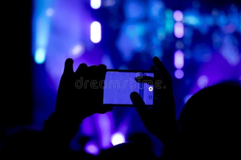 Silhouet van een mensenhand die het overleg met zijn smartphone schieten royalty-vrije stock afbeelding